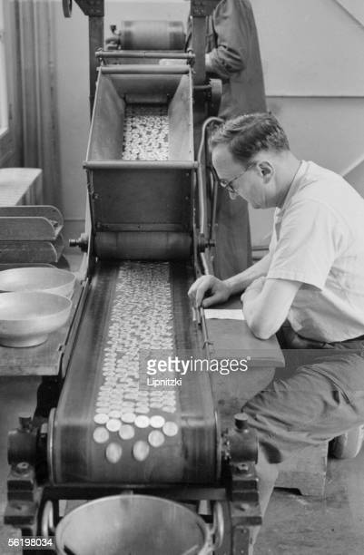 Auditor auditing the coins recently striked to the exit of the conveyor belt Mint of Paris 1959