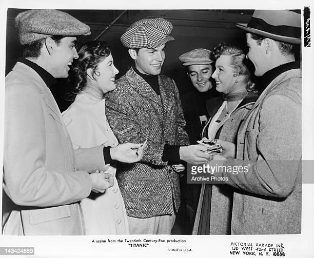 Audrey Dalton and others surrounding Robert Wagner as he exchanges money in a scene from the film 'Titanic' 1953