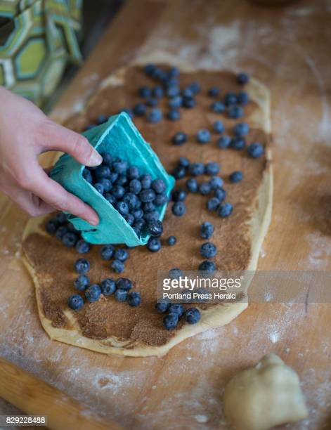 Audrey Farber spills fresh blueberries onto her dough while making rolls at Fork Food Lab