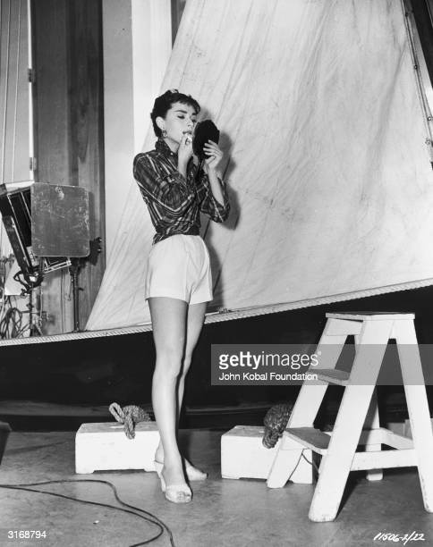 Audrey Hepburn adjusts her makeup off the set of 'Sabrina' directed by Billy Wilder