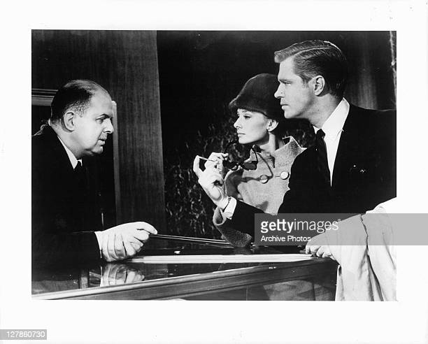 Audrey Hepburn and George Peppard stand at Tiffany's sales counter speaking with John McGiver in a scene from the film 'Breakfast At Tiffany's', 1961.