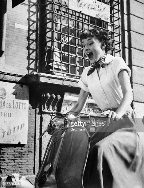 Audrey Hepburn gleefully drives a motorscooter on the set of Roman Holiday