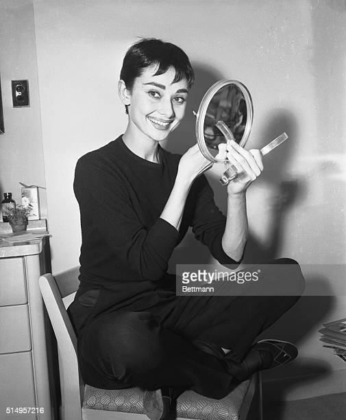 Audrey Hepburn holding a small hand mirror in her dressing room at the 46th Street Theaterapplies makeup for her role in the play Ondine | Location...