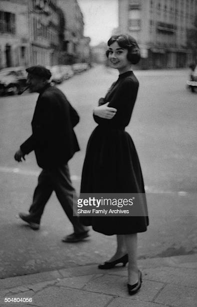 Audrey Hepburn poses in a black dress on the street in 1957 in Paris France