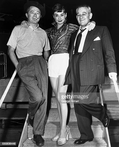 Audrey Hepburn poses prettily between the two men who have produced and directed her Hollywood pictures for paramount Left is Billy Wilder who guided...