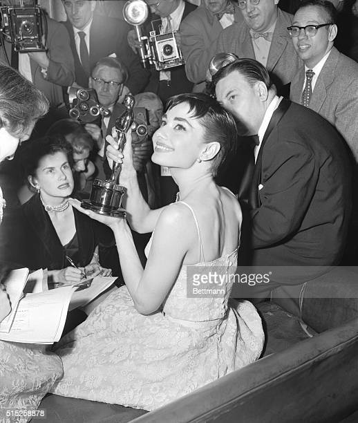 Audrey Hepburn surrounded by photographers and reporters holds up the Academy Award she won for best actress in Roman Holiday her first American film