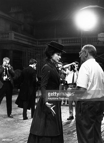 Audrey Hepburn the Belgian born actress dressed in her Eliza Doolittle costume is talking to American film director George Cukor on the Warner set of...
