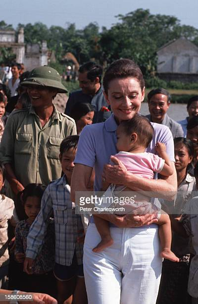 Audrey Hepburn, UNICEF's Goodwill Ambassador, clutches a small Vietnamese baby to her chest as she takes a walk about while visiting a small village...