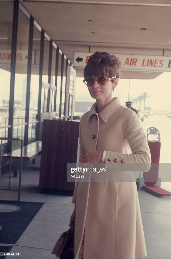 fc8a0dcdca Audrey Hepburn wearing a beige wool coat and sunglasses at the ...