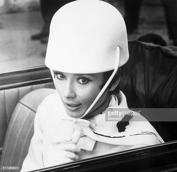 Audrey Hepburn wears a hat that looks like a crash helmet in fabric The hat created as part of her wardrobe for the picture How to Steal a Million...