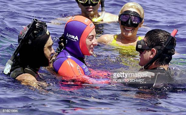 Audrey Mestre Ferreras is congratulated by one her diving assistants Orlando Lanzaz and two official judges from the International Association for...