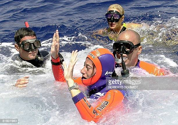Audrey Mestre Ferreras raises her arms as she reaches the surface of the ocean off the coast of Ft. Lauderdale 19 May after succesfully diving to a...