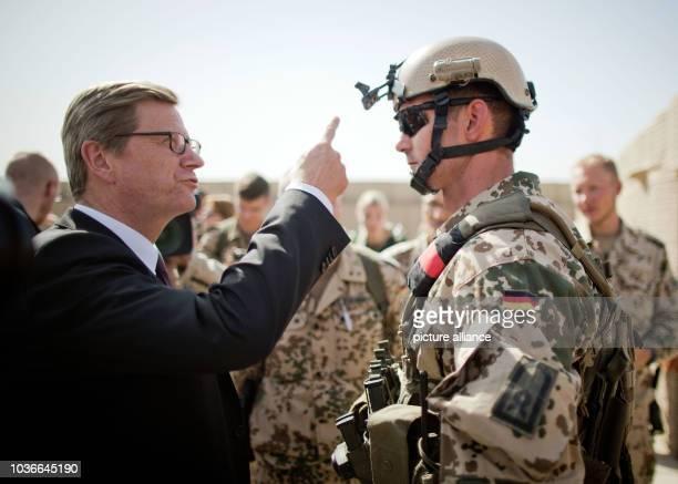 Außenminister Guido Westerwelle spricht am nach seiner Ankunft im Feldlager der Bundeswehr in Kundus in Afghanistan mit einem Soldaten und lässt sich...