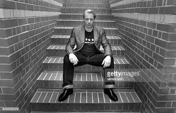 BEN BECKER ZUHAUSE auf den Stufen seiner roten Ziegelsteintreppe an seiner GARTEN WOHNUNG in BERIN MITTE