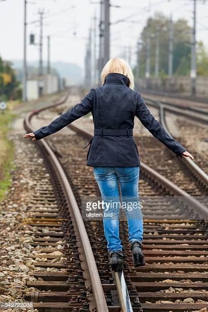 Auf der Suche nach der richtigen Entscheidung balanciert eine junge Frau auf einem Gleis Das Leben stellt die Weichen