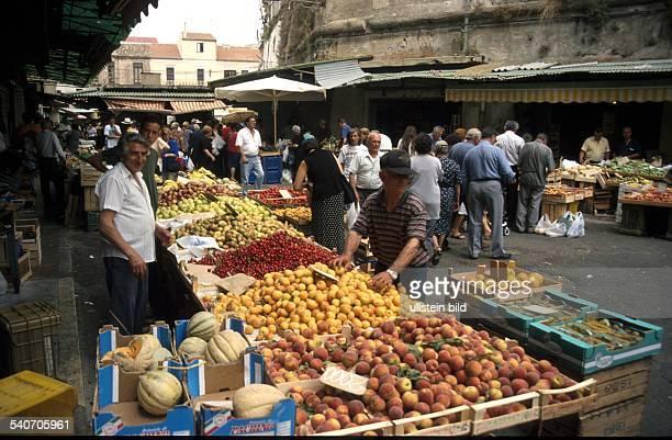 Auf einem gut besuchten Markt in Kalabrien wird an mehreren Ständen frisches Obst und Gemüse angeboten