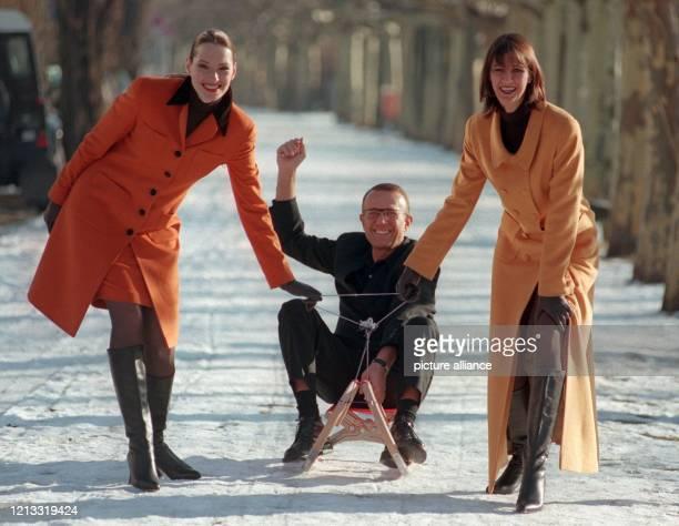 Auf einem Rodelschlitten sitzend, läßt sich Modeschöpfer Tristano Onofri am 16.1.1997 am Düsseldorfer Rheinufer von den Models Tanja und Angela...