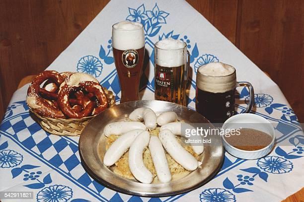 Auf einer blauweiß gemusterten Decke ein Teller mit Weißwürsten auf Sauerkraut Brezeln in einem Korb süßer Senf in einem Porzellanschälchen dahinter...