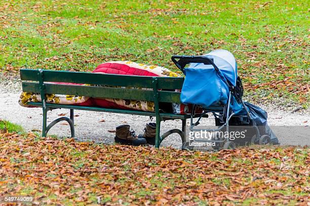 Auf einer Parkbank hat sich ein Obdachloser zum schlafen niedergelegt