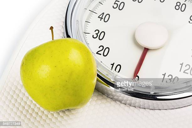 Auf einer Personenwaage liegt ein Apfel Symbolfoto für Abnehmen und gesunde vitaminreiche Ernährung