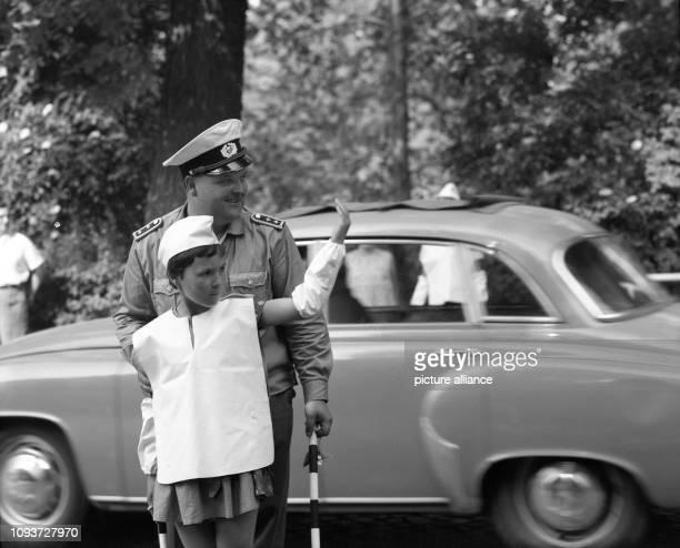 Auf einer Straßenkreuzung in Leipzig darf eine Schülerin im Juli 1977 mit einem Volkspolizisten den Verkehr regeln Kleine Schülerlotsen waren auf an...