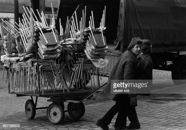 Aufeinandergestapelte Stühle werden per Handkarren transportiert aufgenommen am in der Schönhauser Allee in BerlinPrenzlauer Berg