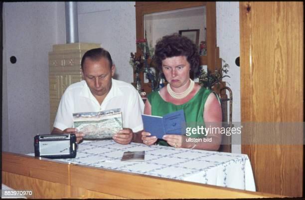 GER Aufnahme ca 1970 Ehepaar bei der Urlaubsplanung Mann mit Urlaubsprospekten von Venedig die Frau mit dem Postsparbuch