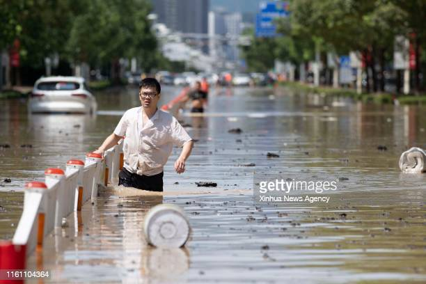 LINHAI Aug 11 2019 A man walks on waterlogged road in Linhai east China's Zhejiang Province Aug 11 2019 More than 21000 service personnel and militia...