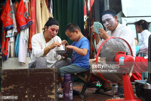 Aug. 16, 2020 -- Ma Xinhua R prepares for a show as his wife Li Fengmin L, also a member of a traditional Yu Opera troupe, takes care of their...