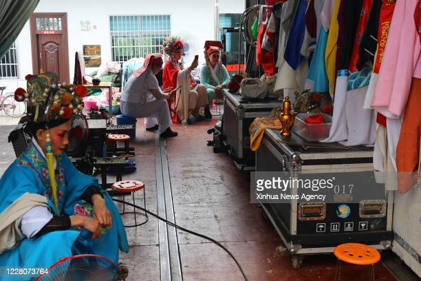 Aug. 16, 2020 -- Members of a traditional Yu Opera troupe have a rest at the backstage in Zhaoyuan Village of Shuangduiji Township, east China's...