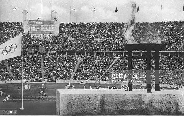 General view of the Olympic Stadium with the Olympic Flame burning in the foreground during athletics events at the 1936 Olympic Games in Berlin...