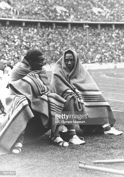 Ralph Metcalfe of the USA and Jesse Owens of the USA competitors in the 100 metres event wrap up warmly on the field at the 1936 Olympic Games in...