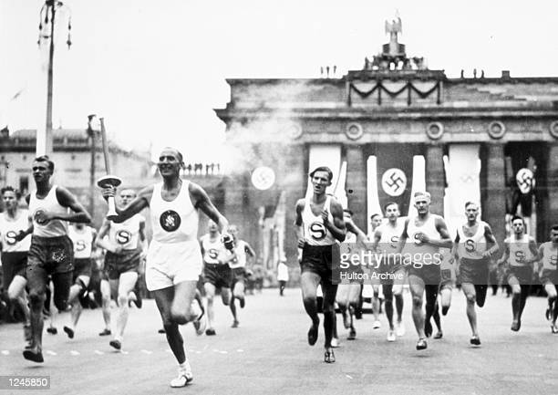 The torch bearer runs through the streets en route to the Olympic Stadium in Berlin Germany Mandatory Credit Allsport Hulton/Archive