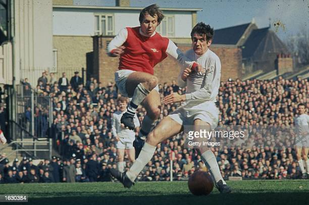 Norman Hunter of Leeds United tackles Court of Arsenal during a Football League Division One match at Highbury Stadium in London Mandatory Credit...