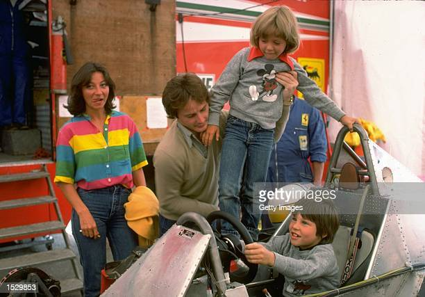 Gilles Villeneuve puts son Jacques at the Controls of his Ferrari Formula One racing car whilst being pictured with his family in the Ferrari paddock...