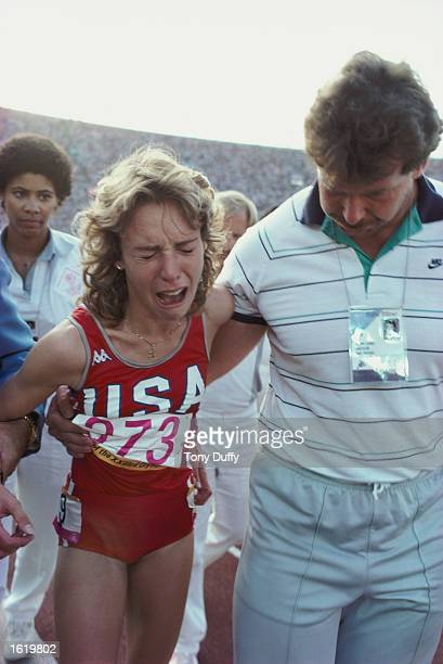 Mary Decker of the USA led away distraught by future husband Richard Slaney of Great Britain after her accidental clash with Zola Budd and consequent...