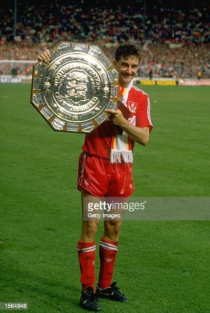 John Aldridge of Liverpool holds the trophy after the Charity Shield match against Wimbledon at Wembley Stadium in London. Liverpool won the match...