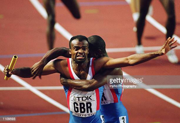 Kris Akabusi of Great Britain crosses the line in first place and is immediately congratulated by teammate Derek Redmond after they won the 4 x 400...