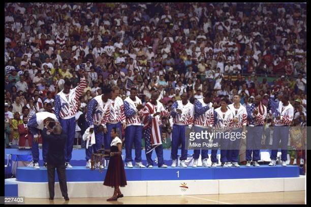 Christian Laettner of the USA Dream Team bends over to receive his gold medal during the medal ceremony following the basketball finals in the 1992...