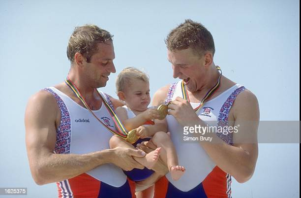 Steven Redgrave and Mathew Pinsent show off their gold medals after the Coxless Pairs holding Steven Redgrave's daughter Natalie Redgrave at the 1992...