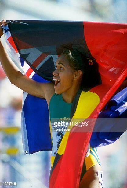 Cathy Freeman of Australia celebrates with both Australian and Aboriginal flags after winning the 400 metres final during the Commonwealth Games in...