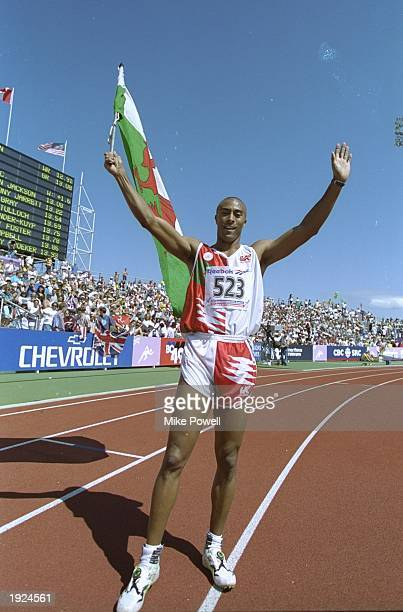 Colin Jackson of Great Britain holds the Welsh Flag aloft after winning the 110 metres Hurdles event during the Commonwealth Games in Victoria,...
