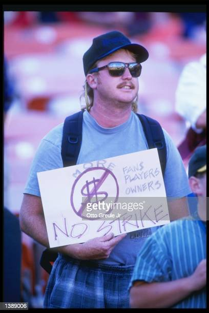 Fan holds up a sign in protest of the baseball strike during a game between the Seattle Mariners and the Oakland Athletics at the Oakland Coliseum in...