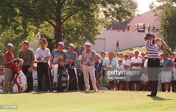GREG NORMAN TEES OFF AS HIS PLAYING PARTNERS NICK PRICE TOM WATSON AND JACK NICKLAUS LOOK ON DURING WEDNESDAY