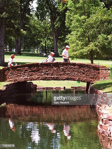 Nick Faldo of Great Britain and his caddie Fanny Sunneson walk across the bridge from the 12th hole during a practice round for the 76th PGA...