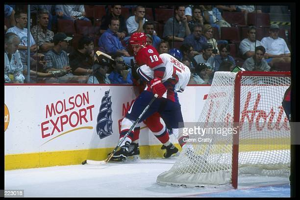 Alexei Yashin of Russia and Marian Smerciak of Slovakia meet at the wall during a World Cup game at the Molson Center in Montreal, Quebec. Russia won...