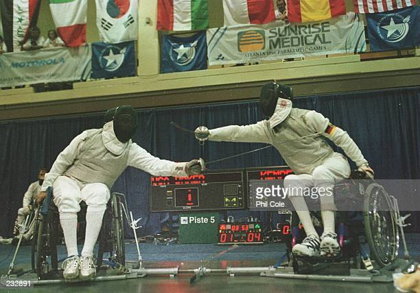 David Baker of the United States battles Wolfgang Kempf of Germany during the men''s fencing portion of the Paralympics held at Mercer University in...