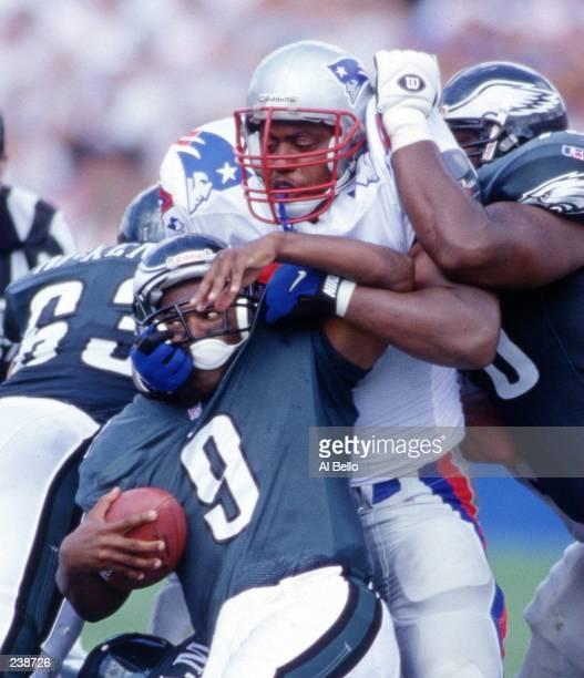 Defensive lineman Mark Wheeler of the New England Patriots twists the helmet off of quarterback Rodney Peete during the Patriots 3710 win at Foxboro...