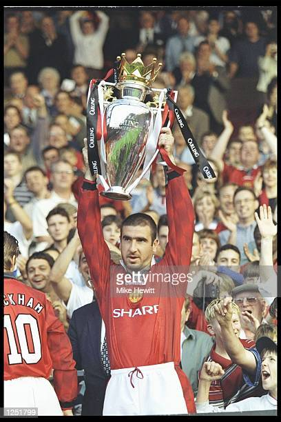 Eric Cantona of Manchester United holds aloft the Premier League trophy before the start of the preseason friendly between Manchester United and...