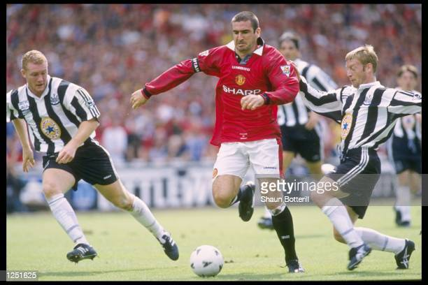 Eric Cantona of Manchester United Is challenged by David Batty of Newcastle United as his teammate Steve Watson looks on during the FA Charity Shield...